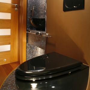 Czarna umywalka, czarny sedes, czarny jest nawet przycisk podtynkowej spłuczki. Do tego błyszczące stalą reling na ręczniki i uchwyt na papier toaletowy.  Fot. Bartosz Jarosz.
