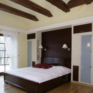 Krokwie przy suficie, szafy wnękowe z frontami z matowego szkła, drewniana podłoga – te elementy występują zarówno w sypialni, jak i przynależnej jej łazience. Fot. Monika Filipiuk.