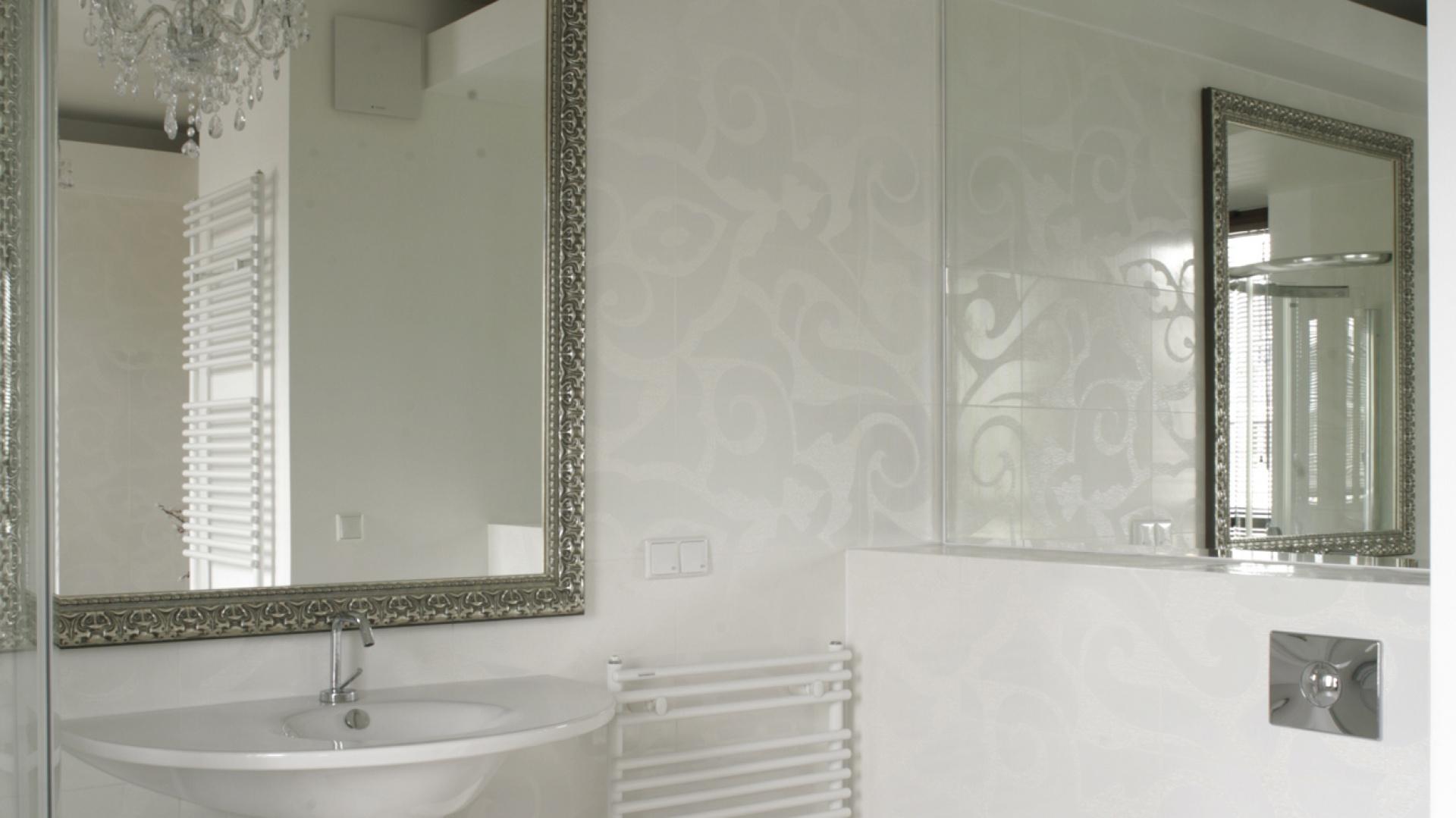 Kafle na ścianach mają kwiatowy wzór typu biel na bieli. Neobarokowa faktura jest widoczna pod światło, także w odbiciach luster. Sprawia, że biel w tej łazience jest przytulna. Fot. Bartosz Jarosz.
