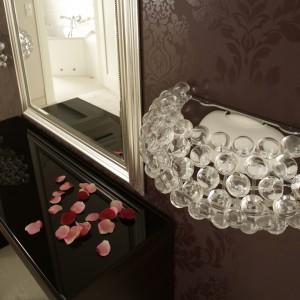 Minimalizm kontra klasyczne inspiracje. Prosty kształt toaletki i posrebrzana rama lustra zestawione z bogatą ornamentyką tapety na ścianie. Po obu stronach lustra umieszczono szklane kinkiety (Caboshe), o eleganckiej, a przy tym lekkiej formie.