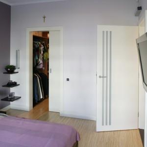 Gospodarze mają do swojej dyspozycji przestronną garderobę, oddzieloną od sypialni przesuwanymi drzwiami. Fot. Bartosz Jarosz.