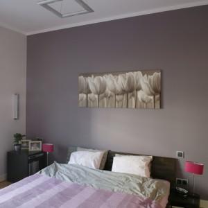 Kolor fioletu i lawendy pojawił się również w sypialni gospodarzy. Korespondują z nim brązowe detale (drewniane łoże i zdjęcie na ścianie), tworząc ciepły, niezwykle przytulny zestaw. Fot. Bartosz Jarosz.