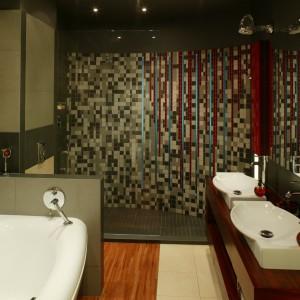 """W półokrągłej kabinie prysznicowej nieregularna mozaika z szarych i grafitowych kostek (Marazzi), przetykana czerwonymi wstawkami i szklanymi """"oknami"""", tworzy motyw wodospadu, podkreślając w ten sposób """"hydrostrefę"""" w łazience. Fot. Bartosz Jarosz."""