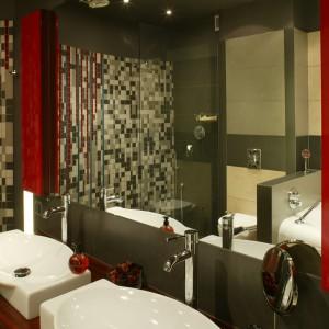Spora przestrzeń łazienki pozwoliła na zamontowanie dwóch umywalek. Właściciele mają również do dyspozycji szafki na kosmetyki i przybory, wbudowane w ścianę i przesłonięte czerwonymi frontami, lakierowanymi na wysoki połysk. Fot. Bartosz Jarosz.