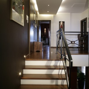 Jedną ze ścian pomalowano na czekoladowy kolor, a sufit obniżono na jednej części, by ukryć dodatkowe oświetlenie. Stopnie schodów pokrywa drewno sukupira, zaś balustradę stworzono ze stalowych, skrzyżowanych elementów. Fot. Monika Filipiuk.