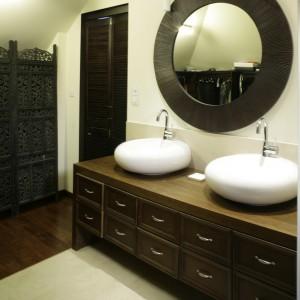 """W pierwszej części salonu łazienkowego znajduje się garderoba, ukryta za drewnianym ażurowym parawanem oraz strefa umywalek. Umywalki są tylko częścią zastosowanej tu kolekcji """"Pure Stone"""", firmy Villeroy and Boch. Fot. Monika Filipiuk."""