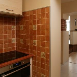 Płytki na ścianach odzwierciedlają wiekowe cegły, pojawiające się w salonie. Dla przeciwwagi wybrano nowoczesną płytę grzejną i piekarnik. Fot. Bartosz Jarosz.