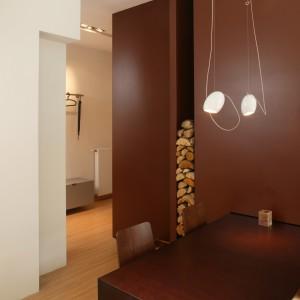 Czekoladowa zabudowa pełni kilka funkcji – oddziela kuchnię i łazienkę, kryje w sobie lodówkę, schowek na drewno, a także wyznacza miejsce stołu. Fot. Bartosz Jarosz.