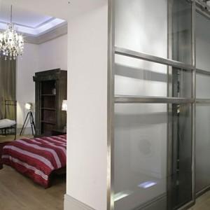 Wrażenie ciemnego, małego przedpokoju, przełamano podwyższając optycznie całość, poprzez wprowadzenie szklanych przesuwanych drzwi w ramach ze stali nierdzewnej. Tworzą one garderobę, dostępną zarówno od strony korytarza, jak i sypialni.