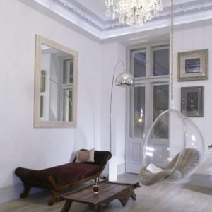 Włoski XIX-wieczny kryształowy żyrandol i polska otomana z 1830 roku. Intrygującymi dodatkami do tego duetu są minimalistyczne sprzęty: stojąca lampa Arco Lamp (proj. Castiglioni z 1962) oraz wiszący fotel Bubble Chair (proj. Aarnio Eero z 1968) – ikony współczesnego designu.