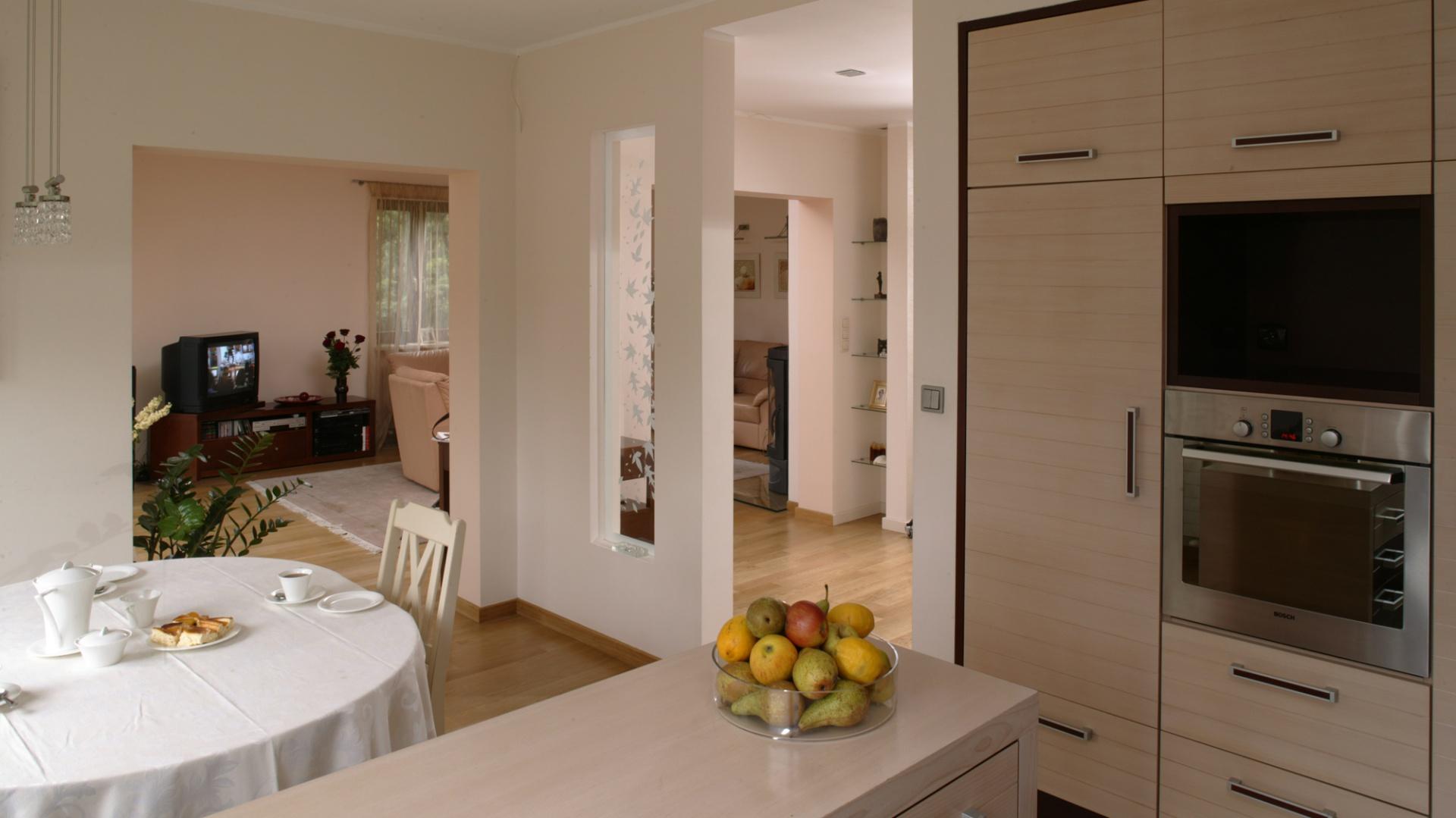 Fronty szafek kuchennych zostały wykonane specjalną techniką pozwalającą na poziome frezowania. Ich powierzchnia wygląda jak połączenie kilku ułożonych poziomo deseczek. W zabudowie – piekarnik marki Bosch. Fot. Bartosz Jarosz.