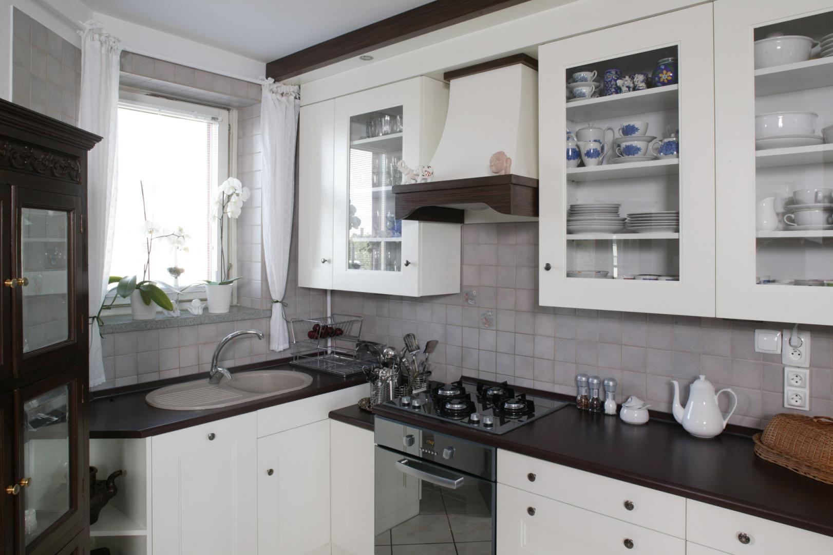 Wzornictwo kuchennej zabudowy subtelnie nawiązuje do stylu retro. Natomiast ciemne elementy – do kolorystyki indyjskich mebli. Fot. Bartosz Jarosz.