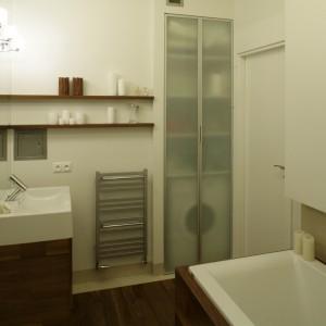 Wanny (Koło) oraz umywalka (Keramag) są obudowane drewnem tekowym. W głębi znajduje się szafka z frontami z satynowanego szkła, w której schowano pralkę oraz łazienkowe akcesoria.