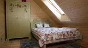 """Drewniany dom z bali, położony na wzgórzu, z którego roztacza się """"widok marzeń"""" niejednego zapracowanego mieszczucha: jezioro, """"dzika przyroda"""", przestrzeń nasycona zapachem ziół."""