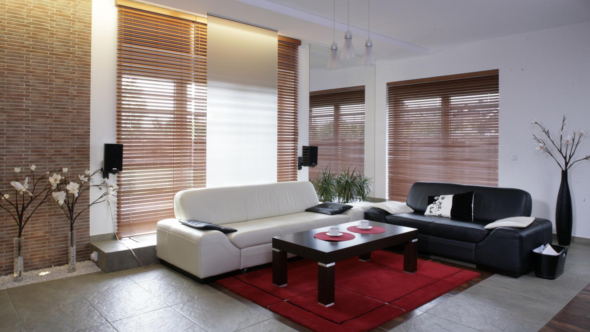 """Zestaw wypoczynkowy (""""Mateo"""", firma Etap) ma prostą formę i szlachetne obicie z miękkiej skóry: kremowej i czarnej. Duże okna zasłaniają drewniane żaluzje, a także specjalnie zaprojektowana ścianka ze szkła matowego, na potrzebę komfortowego oglądania TV. Fot. Monika Filipiuk."""