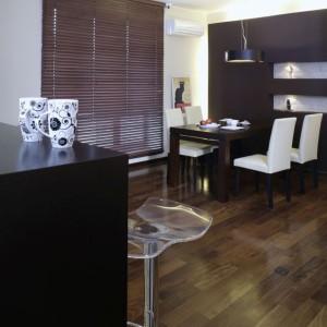 Kącik jadalniany to integralna strefa salonu. Skupia się wokół jednej z dwóch dekoracyjnych ścianek, w kolorze gorzkiej czekolady. Stół i krzesła pochodzą ze sklepu Agata Meble. Fot. Monika Filipiuk.