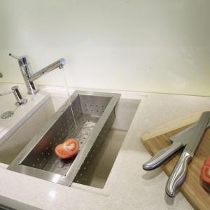 Szkło czyni wnętrze optycznie lżejszym. Pojawia się w kuchni na frontach wiszących szafeczek, a także jako zabezpieczenie ściany przy zlewie. Fot. Monika Filipiuk.