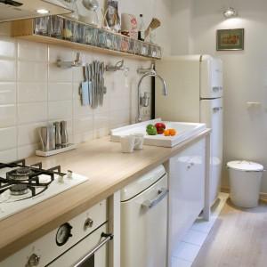 Podłoga z dębowych desek sięga niemal do kuchennej zabudowy. Jest tu niewiele szafek, utensylia zawisły więc na ścianie. Sypkie produkty przechowywane są w pojemnikach z Ikei, noże trzymają się ściany dzięki magnesowi. Fot. Monika Filipiuk.