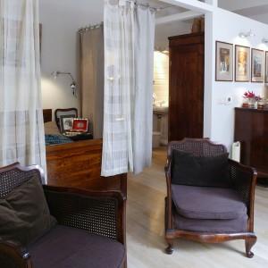 Mieszkanie ma charakter otwarty. Sypialnię od salonu oddzielają lniane zasłony. Dalej przechodzi się do gotowalni i części kąpielowej, także przesłoniętych jedynie kotarami. Fot. Monika Filipiuk.