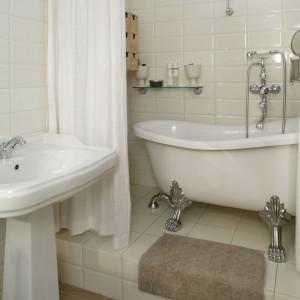 """Wyposażenie łazienki w stylu retro to sprzęty współczesne. Umywalka oraz wanna zostały wybrane z oferty firmy GSI, zaś armatura – Tres. Płytki, z charakterystycznymi napisami, to kolekcja """"Pun"""" Ascot Ceramiche. Fot. Monika Filipiuk."""