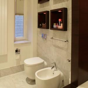 Dwa rzędy  drewnianych kubików  zdobią łazienkę, przydają się też  jako praktyczne półeczki. Atmosferę dopełniają halogenowe źródła światła ukryte w drewnianych skrzyneczkach osadzonych w ścianie. Fot. Bartosz Jarosz.
