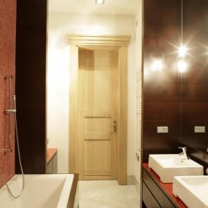 Drzwi wejściowe do łazienki w całości wykonane są  z drewna dębowego, olejowanego na biało, dodatkowo pokrywa patyna. Futrynę wieńczy ozdobny gzyms.  Drzwi są jednym z wielu detali zaprojektowanych specjalnie do tego wnętrza. Fot. Bartosz Jarosz.