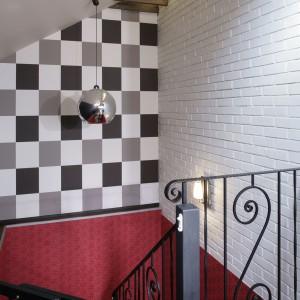 Do stylu glamour nawiązuje ozdobna poręcz przy schodach. Śmiałe połączenie szarości szachownicy i czerwonej, wzorzystej tapety na ścianach klatki schodowej dało zaskakujący efekt. Fot. Monika Filipiuk.