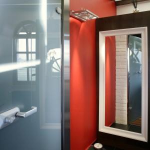 Wykończona fornirem dębowym ścianka działowa mieści wysuwane carga, które w niewielkiej łazience pełnią rolę szafki łazienkowej. Po wysunięciu zastępują również półki w kabinie. Drzwi prysznicowe marki Koło. Fot. Monika Filipiuk-Obałek.