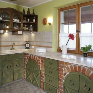 Pogodny, sielski charakter kuchni gwarantuje m.in kolor ścian: pastelowy seledyn rozjaśnia wnętrze i dobrze koresponduje z czerwienią cegieł i ciemną zielenią drzwiczek. Fot. Monika Filipuk.