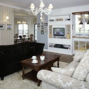"""Tapety na ścianach salonu oraz wzory na kanapie i dywanie nie pozostawiają wątpliwości, że mamy do czynienia z wnętrzem w angielskim stylu. Za """"oknem"""" wypełnionym witrażowym szkłem znajduje się wnętrze kuchni. Fot. Monika Filipiuk."""