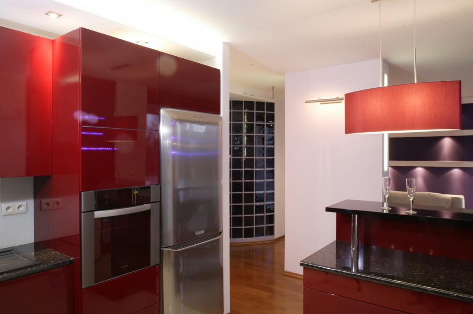Bar od strony kuchni został wyposażony w półkę, na której można ustawić np. szklanki i kieliszki. W tle widok na salon i wyjście na korytarz, ozdobione półokrągłą ścianą z luksferów. Fot. Monika Filipiuk.