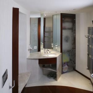 Zabudowa umywalki, tak jak cały wystrój łazienki, ma rzeźbiarski,  artystyczny szlif. Jasne powierzchnie to marmur i tynk naśladujący trawertyn (firmy Oikos), zaś ciemne – drewno jatoba. Fot. Monika Filipiuk.
