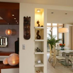 Salon i jadalnia to ewidentny przykład na udane połączenie egzotyki z nowoczesnością. Jasna kolorystyka części jadalnianej (na podłodze ułożono na przemian matowe i polerowane płytki) kontrastuje z ciemniejszym salonem, w którym główną rolę gra drewno. Fot. Bartosz Jarosz.