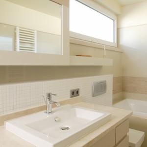 Kubistyczna umywalka, sedes i wanna (Duravit) doskonale wpisują się w przyjętą w łazience surową, naturalną stylistykę. Aby maksymalnie wykorzystać przestrzeń, a jednocześnie optycznie powiększyć przestrzeń, front szafki górnej pokryto lustrem, a ścianę w okolicy umywalki wyłożono białą mozaiką. Fot. Bartosz Jarosz.