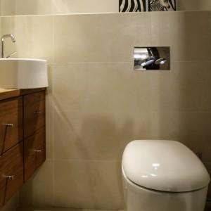 Toaleta została pokryta tylko i wyłącznie płytkami w kolorze écru. Drewniana szafka podumywalkowa jest tu jedynym elementem o zdecydowanej barwie. Fot. Monika Filipiuk.