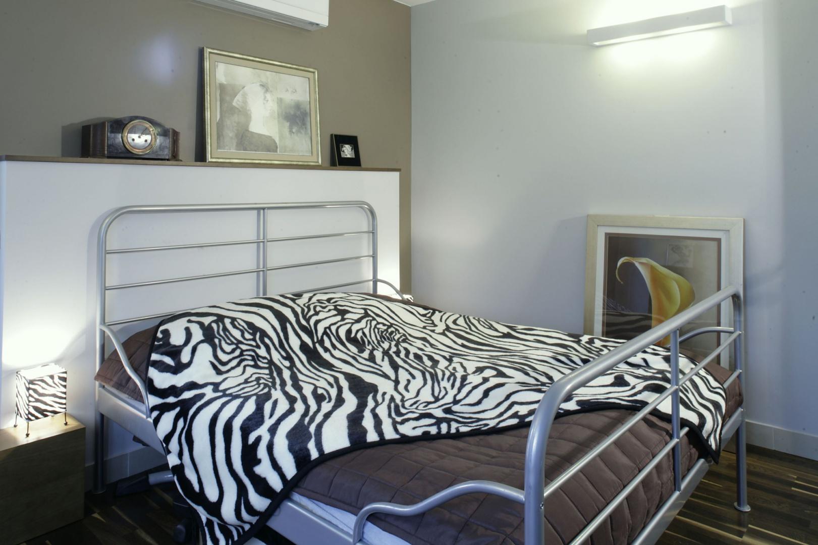 Paski zebry rozgościły się także w małżeńskiej sypialni, przejmując w posiadanie narzutę oraz abażury lampek nocnych. Ściany sypialni pomalowano na odcienie chłodnego kakao, bieli i szarości. Fot. Monika Filipiuk.