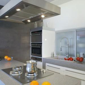 Nowoczesny rys nadają kuchni sprzęty AGD oraz dodatki w stalowym wykończeniu. Bateria z wysoką wylewką nie blokuje dostępu do szafki, ponieważ szklane fronty można przesunąć. Fot. Monika Filipiuk.