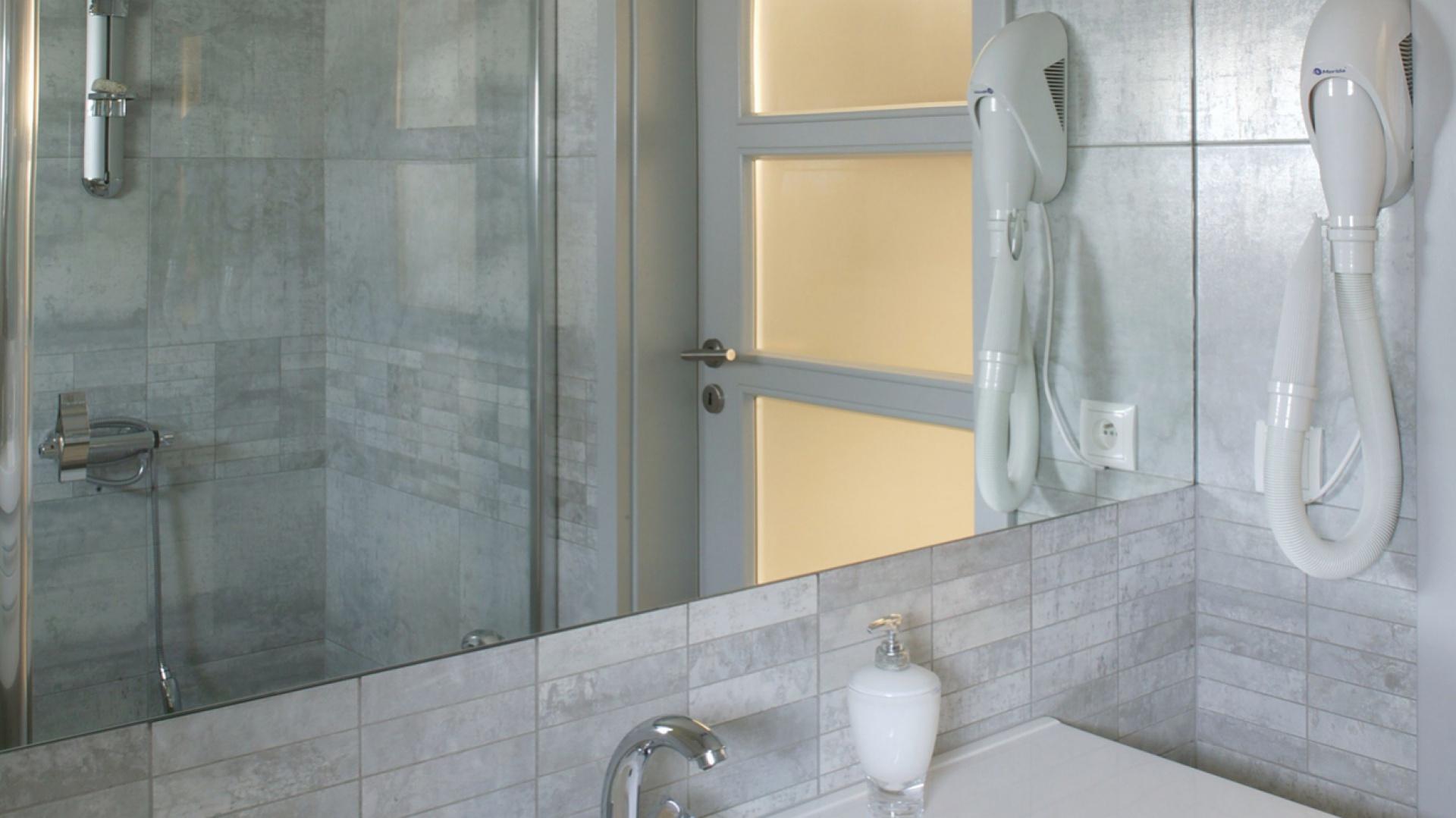 Konsekwencja w doborze kolorów i materiałów została zachowana w całym domu. Szare płytki gresowe, z których ułożono większość podłóg, wykorzystane są w również w łazience (tu zagrano jednak ich rozmiarami). Fot. Monika Filipiuk.