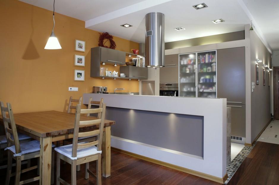 Niska ścianka jest wyraźnym elementem oddzielającym część kuchenną od jadalni. Klarowność tego podziału podkreślają linie podwieszanego sufitu i podłogi. Fot. Monika Filipiuk.