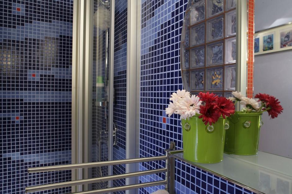 """Wszechobecna mozaika firmy Appiani stwarza wrażenie morskich głębin, stalowe akcesoria łazienkowe i bateria prysznicowa """"Meta"""" Dornbracht podkreślają jej niebieskie odcienie. Fot. Monika Filipiuk."""