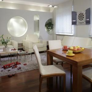 Strefę jadalnianą zajmuje drewniany, rozsuwany stół i jasne krzesła (BoConcept) ustawione na eleganckim, drewnianym parkiecie. W tle widać tablicę do gry w strzałki, która idealnie wpasowuje się w nowoczesne wnętrze. Fot. Monika Filipiuk.