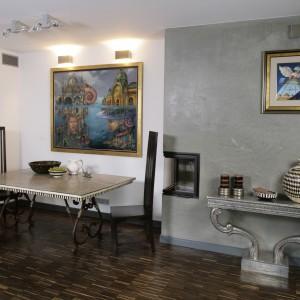W stanowiącym część salonu kąciku jadalnianym, króluje oryginalny, delikatny w konstrukcji stół z ciężkimi, drewnianymi krzesłami. Zawieszony nad nim obraz, został od góry podświetlony. Blask padający z prostokątnych kinkietów oświetla całą strefę jadalnianą. Fot. Bartosz Jarosz.