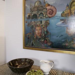 Obrazy we wnętrzu oświetlono od góry kwadratowymi lampami. Ich blask pada także na strefę jadalnianą. Fot. Bartosz Jarosz.