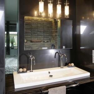 W niszy powstałej przez zmniejszenie szafy sypialnianej zamontowana została umywalka (Duravit). Ściana przy niej obudowana jest połyskującymi płytkami. Fot. Bartosz Jarosz.