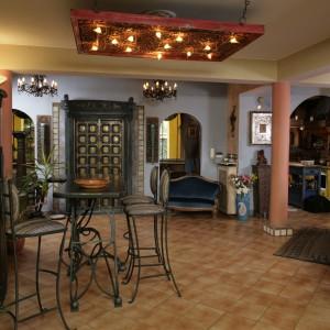 Stylowy bar powstał z połączenia dwóch starych mebli kuchennych. Oryginalna lampa nad nim to autorskie dzieło pana domu. W tle widać wspaniałe indyjskie drzwi. Fot. Bartosz Jarosz.