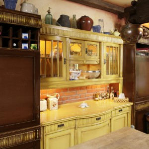 Kuchnia to ciekawe połączenie starego z nowym oraz nieszablonowy miszmasz kolorystyczny. Ściany częściowo wyłożono cegłami, pochodzącymi z rozbiórki mazurskiej stodoły. Fot. Bartosz Jarosz.
