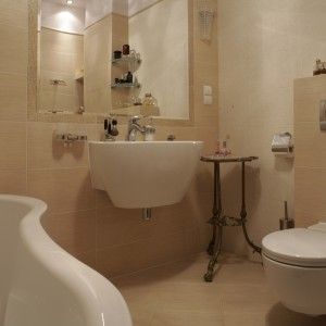 Płytki gresowe, którymi wyłożona jest łazienka, nadają wnętrzu wytworny wygląd. Dzięki temu stylowe elementy wystroju, między innymi stoliczek w rogu pomieszczenia, czuja się tutaj dobrze. Fot. Monika Filipiuk.