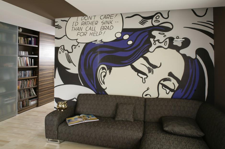 Ściana za kanapą ozdobiona jest tapetą z reprodukcją obrazu Roya Lichtensteina i podświetlona dwoma geometrycznymi kinkietami (Aquaform). Przy wyłączonym świetle kinkiety są prawie niewidoczne. Fot. Bartosz Jarosz.