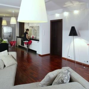 Salon, kuchnia oraz jadalnia tworzą obszerną, otwartą przestrzeń. Kompozycyjnie spina je jednolita powierzchnia podłogi wyłożona parkietem z egzotycznego drewna iroko. Fot. Monika Filipiuk.