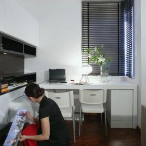 W kąciku do pracy uwagę przyciągają designerskie przedmioty, jak chociażby okrągła lampka (Falko). W wykonanym na zamówienie biurku zamontowane zostały  dodatkowo dwie boczne szafki. Fot. Monika Filipiuk.